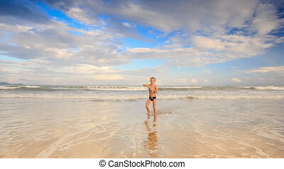 Little Blond Boy Gambols in Shallow Water on Sand Beach