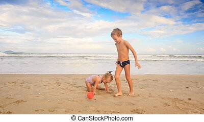Small Girl with Pigtail Somersaults Boy Runs around on Beach...