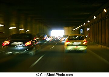 Cars moving traffic with brurred  blur headlights on the tunnel