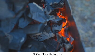 Coal burning in a brazier grill. - In a lot of smoldering...