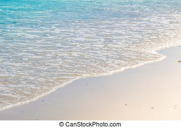 Soft wave of blue ocean on wet sandy beach. Background