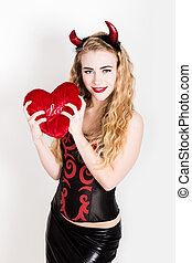 Young and beautiful curly girl with red horns looks like pretty Devil, holding a heart pillow