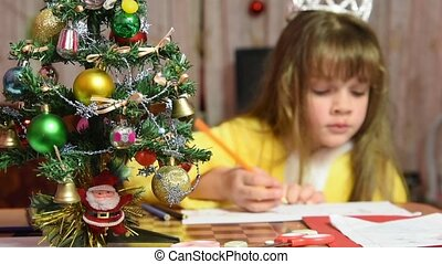 The girl draws at the table Christmas pattern, focusing on...