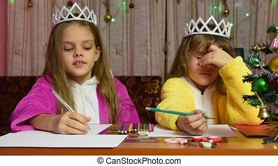 Two girls in dressing gowns sitting at a table and writing a letter to Santa Claus, one of them thinks funny
