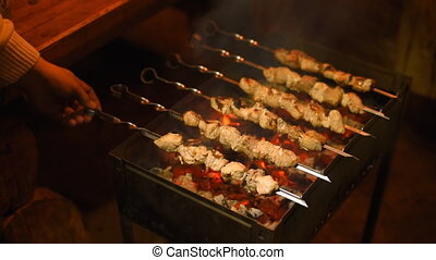 Roasting shish kebabs on the grill. The play of light,...