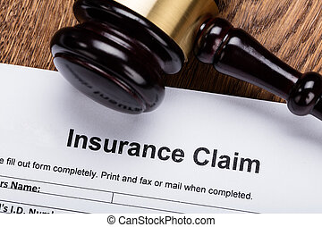 Wooden Gavel On Insurance Claim Form - Close-up Of Wooden...