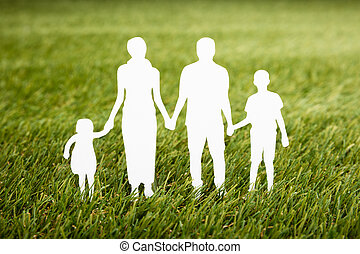 Family Papercut On Grassy Field - Close-up Of Family...