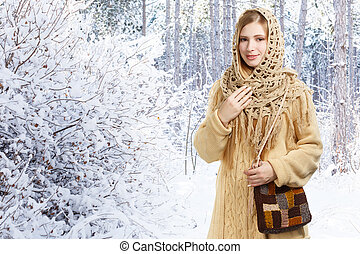 Young smiling stylish woman in openwork shawl and long beige sweater with checkered motley knitted bag stands in winter snowy forest.