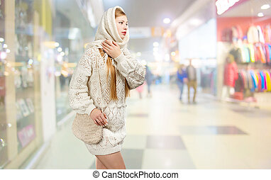 Young smiling stylish blonde woman in white knitted scarf with fringe and long patterned sweater with crocheted bag in hands walks in shopping centre.