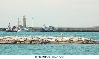 Lighthouse and boats. Water, stones and sky. Sea travel on...
