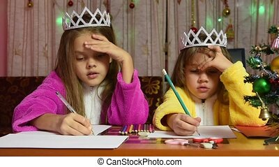 Two girls in dressing gowns sitting at a table and writing a letter to Santa Claus