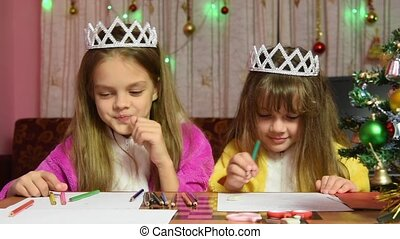 Sisters swearing and jostling drawing at a table in a...
