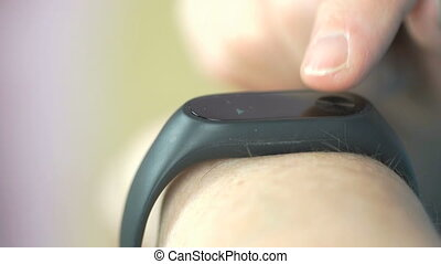 Woman touches wristband of pulse monitor indoors - Wristband...