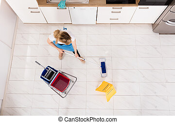 Housemaid Mopping Floor In Kitchen - High Angle View Of...