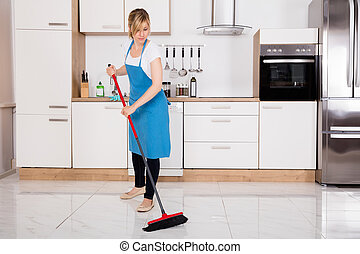 Housemaid Sweeping Floor In Kitchen - Young Cleaner...