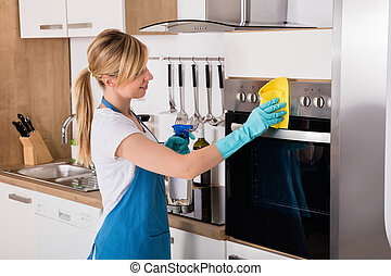 Housemaid Cleaning Oven In Kitchen - Young Housemaid Service...