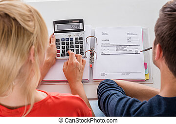 Couple Calculating Invoice - Close-up Of Couple Calculating...