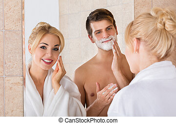 Man Shaving And Her Wife Cleaning Her Face