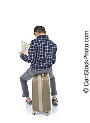 Back of Asian boy sitting on lugguage and holding map on white background.  Travel concept
