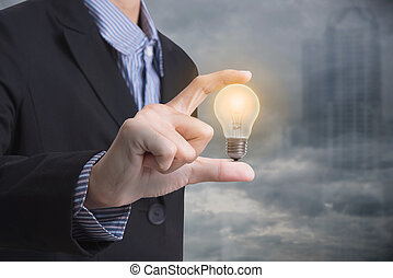 Business hand holding illuminated light bulb concept for idea, innovation and inspiration for business