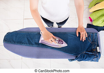 High Angle View Of Woman Ironing Jeans - High Angle View Of...