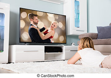 Woman Watching Movie On Television - Young Woman Lying On...
