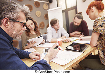 Mature man using smartphone during the business meeting