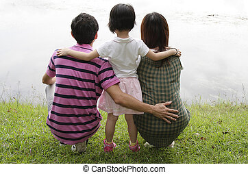 Family by a lake - Rear view of an Asian family by a lake