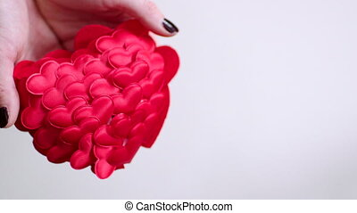 Hands throwing red heart and it crashing - Woman's hands...