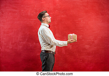 Young funny man with gift on red studio background