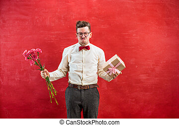 Young funny man with flowers and gift - Young disappointed...