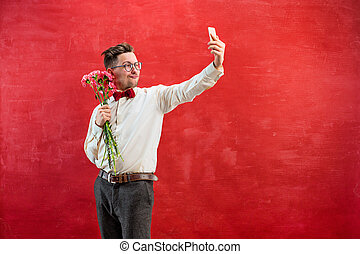 Young beautiful man with flowers and phone making selfie on...
