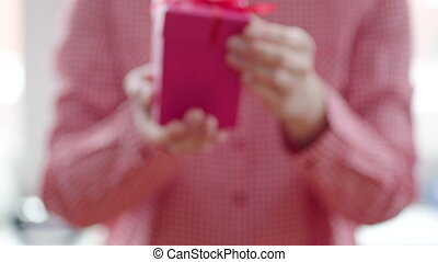 Woman opening holiday gift with red ribbon and light inside...