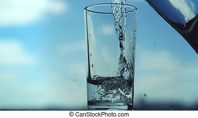 Pouring water in glass on blurred blue sky background. -...
