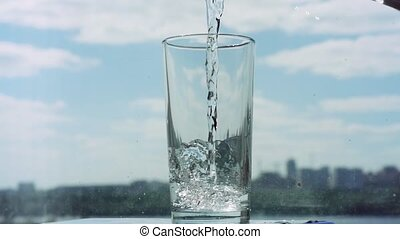 Pouring water in glass in slowmotion on blurred city and blue sky background. 1920x1080