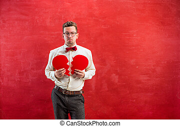 Young funny man with abstract broken heart - The young funny...