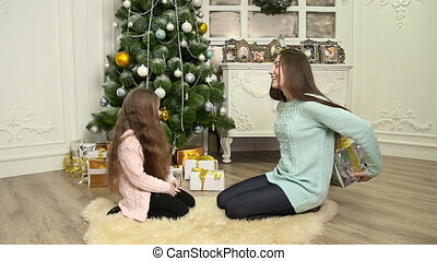 mother gave her daughter a gift near the Christmas tree