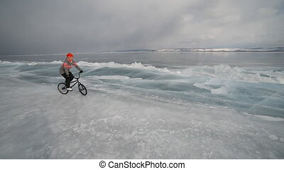 The girl goes on a bmx on ice. - The girl goes on a bmx on...