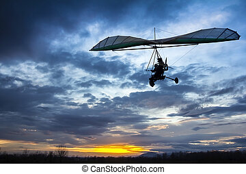 Motorized hang glider flying in the sunset