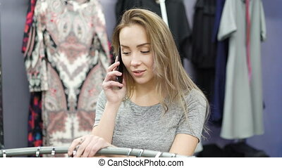Pretty girl talking on the phone in a clothing store