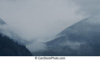 Mist Swirling Over Vast Mountain Landscape - Thick mist over...