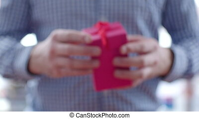 Man giving a gift in pink box with red ribbon - Close up of...