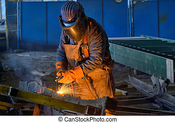 Welder welding metal in plant