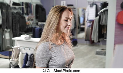 Pretty girl receiving packaging with clothes at cash...