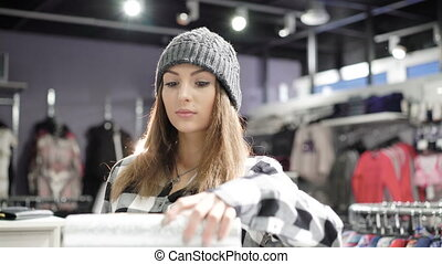 Stylish girl looking on clutch in fashionable boutique. 4K -...