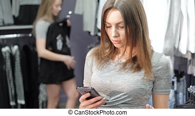 Woman holding a credit card and using mobile phone for...
