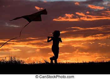 A young girl runs to try and fly her kite at sunset.