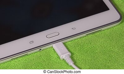 Hand unplugging white usb cable from smart tablet computer...