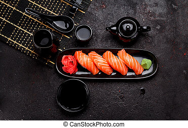 Japanese cuisine. Salmon sushi (nigiri) on a black plate and...