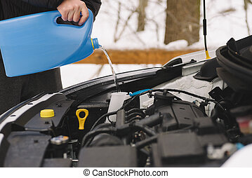 Man pouring car winter windshield washer fluid